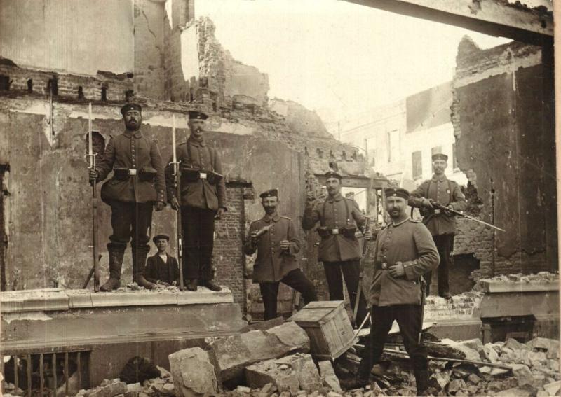 Duitse manschappen poseren bij een uitgebrand gebouw op het stationsplein in Leuven (foto Stadsarchief Leuven)