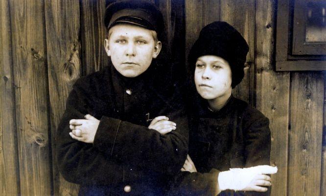 Op 19 september 1914 bevinden twee jonge kinderen Marie Louise (9j.) en Bernard (7j) Mahy zich in een Duits gevangenkamp. Mogelijk behoren zij tot het gezin Mahy waarvan vader Jan op 25 augustus 1914 voor ogen van zijn vrouw en kinderen in koelen bloede is afgemaakt.  Marie-Louise is tot 29 september in het gevangenekamp gebleven, haar jongere broer zelfs tot 31 januari 1915. Er zijn verschillende foto's bekend van willekeurig opgepakte burgers die in de Duitse kampen van Soltau, Celle of Munster tijdens de eerste oorlogswinter gevangen zijn gehouden. Deze aangrijpende foto toont twee jonge kinderen in het gevangenekamp Munster. Hun identiteit is onbekend. Misschien hebben Marie Louise en Bernard deze kinderen wel gekend? Misschien hebben ze zich samen proberen warm te houden tijdens die koude wintermaanden van 1914-15? Of hebben ze samen gebikkeld naast hun houten kampbarak, om uit de wind te zitten…
